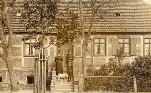 Vergilbtes Foto des alten Fachwerkhauses mit Gutsbesitzerfamilie in dunkler Kleidung auf der Vortreppe
